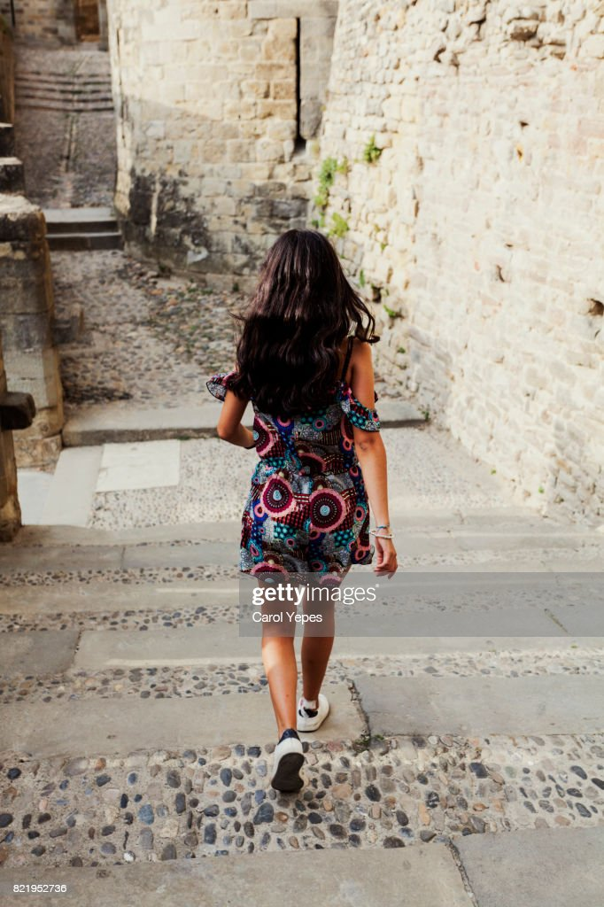 rear view young tourist walking  away in an Italian village : Stock Photo