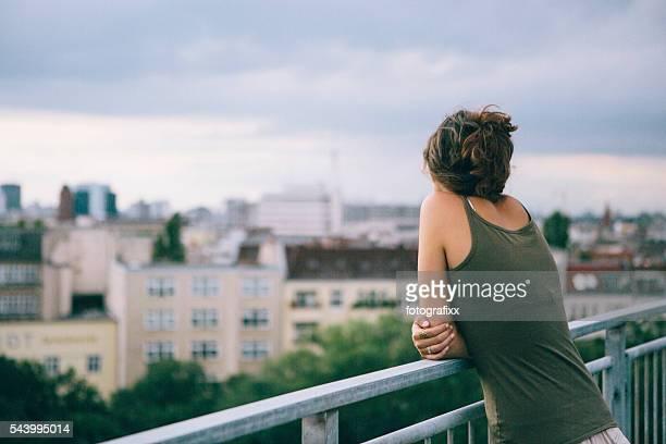 Rückansicht: Junge Frau lehnt sich gegen Geländer, sieht aus zu Skyline