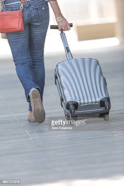 Rear waist down view of mature woman leaving hotel with wheeled suitcase