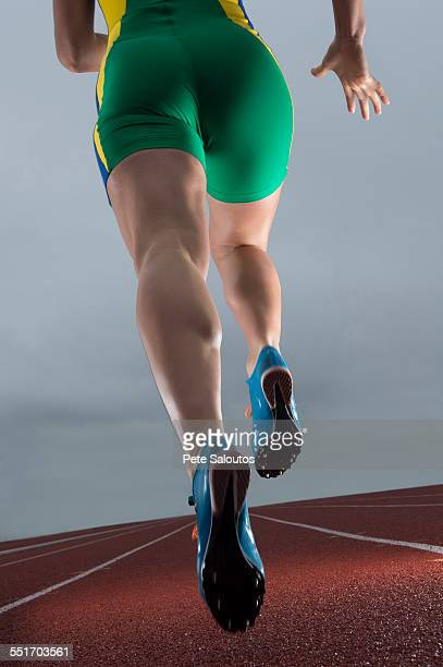 Rear waist down view of young female athlete running on race track
