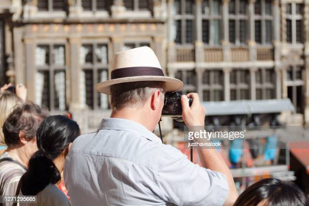 rearshot of caucasian mature man with straw hat photographing grand place with flower carpet - capital region stock pictures, royalty-free photos & images