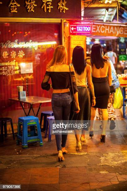 rearshot of three walking thai transgenders in khaosan road - ladyboys stock pictures, royalty-free photos & images