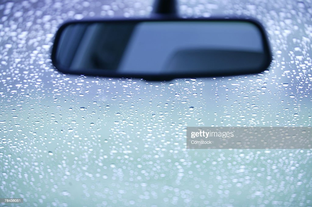 Rearview mirror and rain on a windshield : Stock Photo