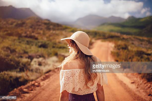 rearview of boho girl standing on dirt road in summer - beige hat stock photos and pictures
