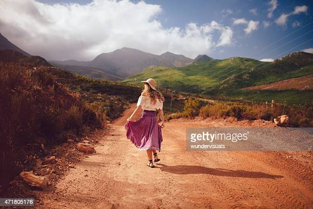 rearview of boho girl walking down a country dirt road - beige hat stock photos and pictures