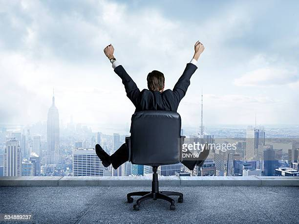Rearview of businessman sitting in chair with outstretched arms.