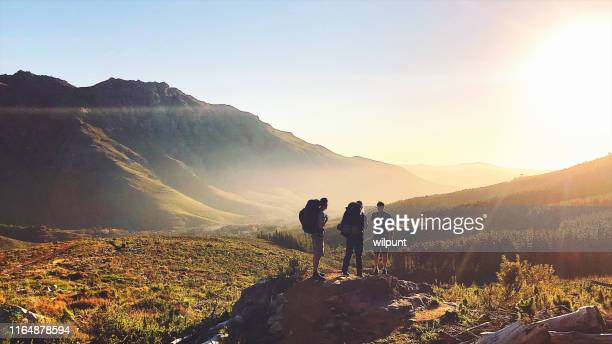 rearview of hikers with backpacks enjoying the sunset in the mountains - summit stock pictures, royalty-free photos & images