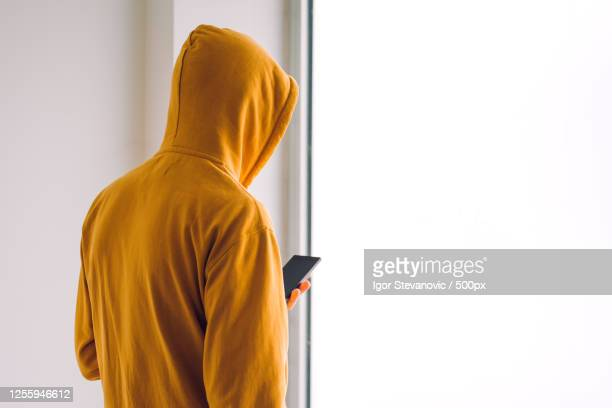 rearview of man with hoodie and mobile phone standing by the window - identity theft stock pictures, royalty-free photos & images