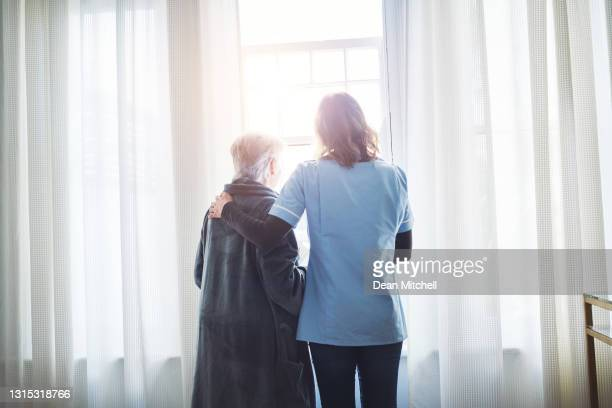 rearview shot of a young nurse assisting a senior woman while looking out a window in a retirement home - human body part stock pictures, royalty-free photos & images
