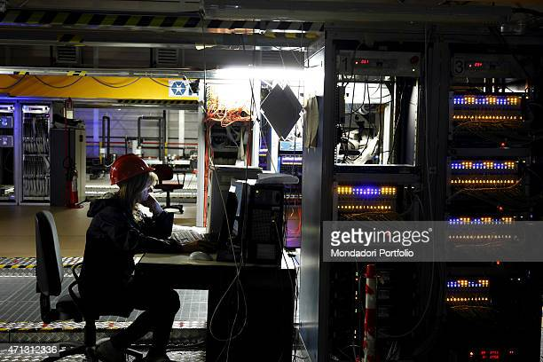 Reasearcher seated in front of a computer among the machines and equipments of the nuclear physics laboratory under Gran Sasso. Assergi , Italy,...