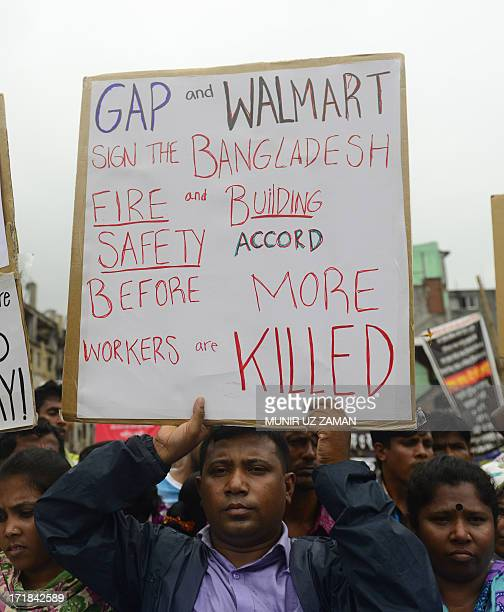 Reatives of Bangladeshi workers who lost their lives in a garment factory disaster shout slogans as they gather with banners and placards in Savar on...