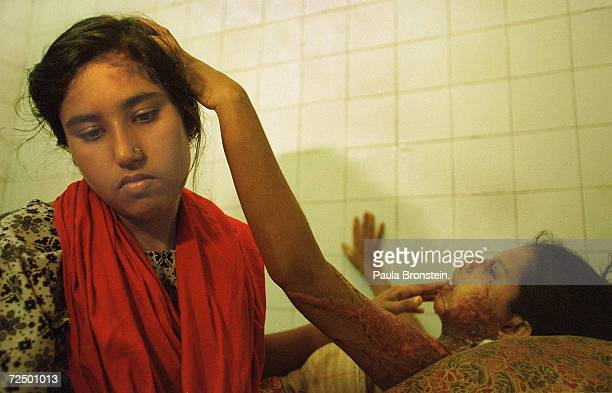 Reba right a 19 yearold Bangladeshi woman lies with her arms outstretched July 2000 in Dhaka Bangladesh as her sister Nahehma tends to her wounds...