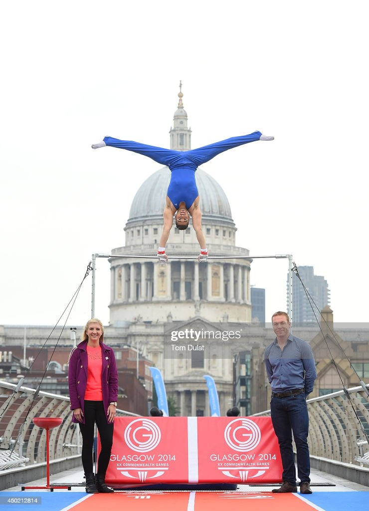Rebecca Adlington (L) and Sir Chris Hoy (R) pose for photos as Olympic silver medalist Louis Smith MBE performs on a high bar during the Glasgow 2014 Commonwealth Games Media Launch at the Millenium Bridge on June 7, 2014 in London, England.
