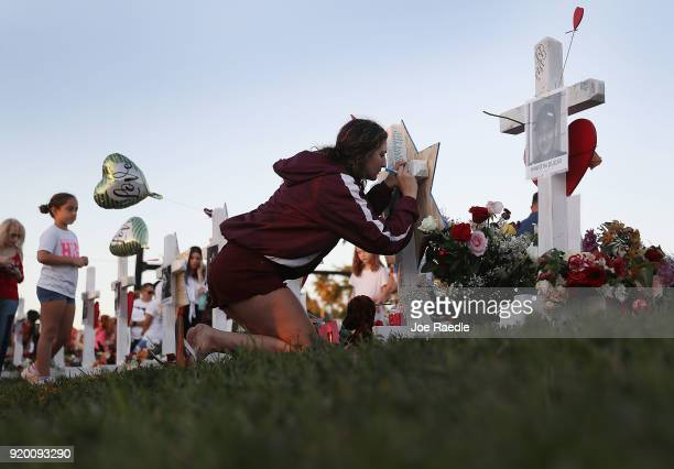 Rebecca Bogart a senior at Marjory Stoneman Douglas High School writes a note on a makeshift memorial setup in front of the school on February 18...