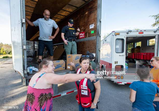 Rebecca DeLorenzo assists Laurie Allison get a case of instant hot meals after Hurricane Michael on October 12 2018 in Carrabelle Florida At least 17...