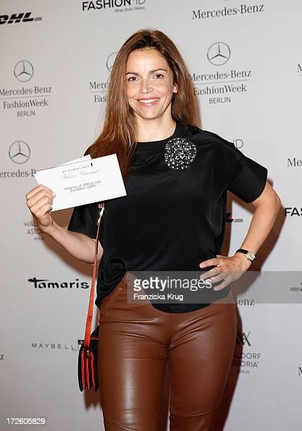 Rebecca Immanuel shows her invitation prior to the Schumacher Show during MercedesBenz Fashion Week Spring/Summer 2014 at the Brandenburg Gate on...