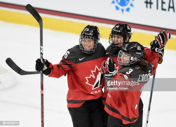 Rebecca Johnston Brianne Jenner and Jocelyne Larocque of Canada celebrate winning the game against the United States in overtime on December 3 2017...