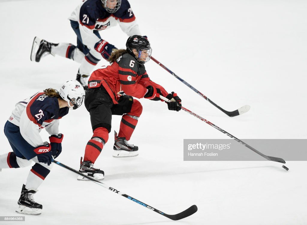 Rebecca Johnston #6 of Canada controls the puck against Alex Carpenter #25 and Hilary Knight #21 of the United States in overtime of the game on December 3, 2017 at Xcel Energy Center in St Paul, Minnesota. Canada defeated the United States 2-1 in overtime.
