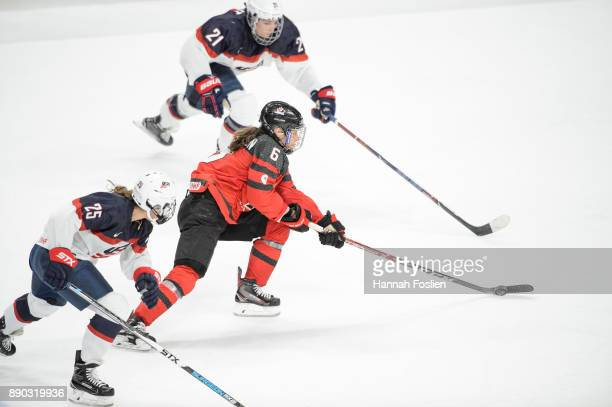 Rebecca Johnston of Canada controls the puck against Alex Carpenter and Hilary Knight of the United States during the game on December 3 2017 at Xcel...