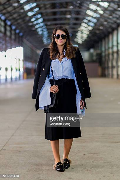 Rebecca Karagiorgos wearing a baby blue button shirt with oversized sleeves a black blazer bag sunglasses and skirt and Gucci slippers outside Ginger...