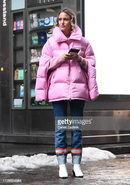 Rebecca Laurey is seen wearing a pink puff coat and color block jeans and white boots outside the Michael Kors show during New York Fashion Week:...