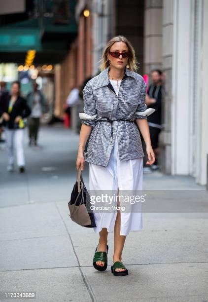 Rebecca Laurey is seen wearing white dress with slit, grey belted blazer outside Tibi during New York Fashion Week September 2019 on September 08,...