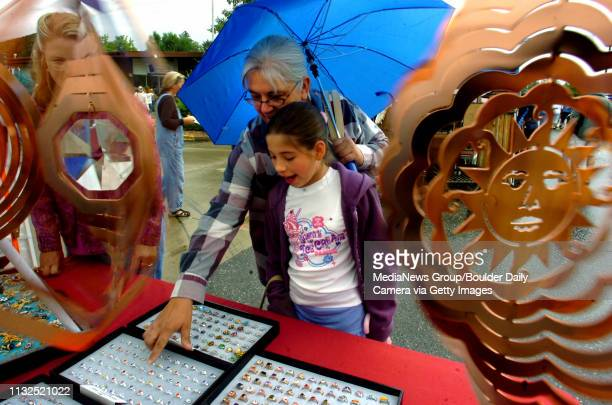 Rebecca Lopez gets help from Denise Higgins while selecting jewelry from Don and Connie Buchanan's boothThe seventh annual Lafayette Peach Festival...