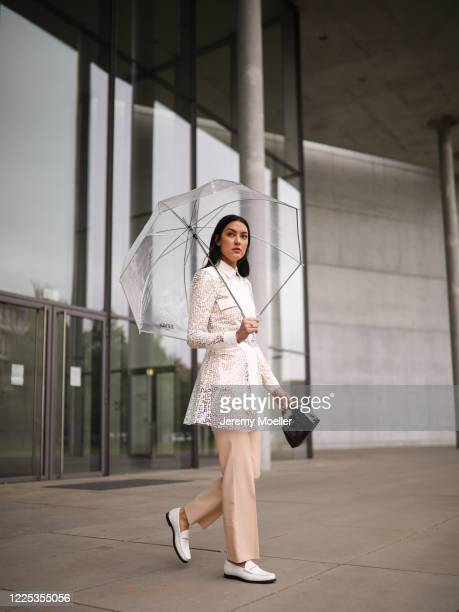 Rebecca Mir wearing Drykorn suit Longchamp rain coat and bag and Jimmy Choo loafer on May 13 2020 in Munich Germany