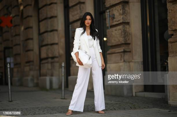 Rebecca Mir wearing Max Mara suit and bag, Atelier Swarovski jewelry and Midnight 00 heels on July 21, 2020 in Munich, Germany.