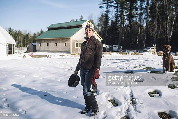 Rebecca Nelson with her chickens' water bowl, and dog Dalton on her property in Scarborough, ME on Tuesday, December 2, 2014. Nelson raises turkeys,...