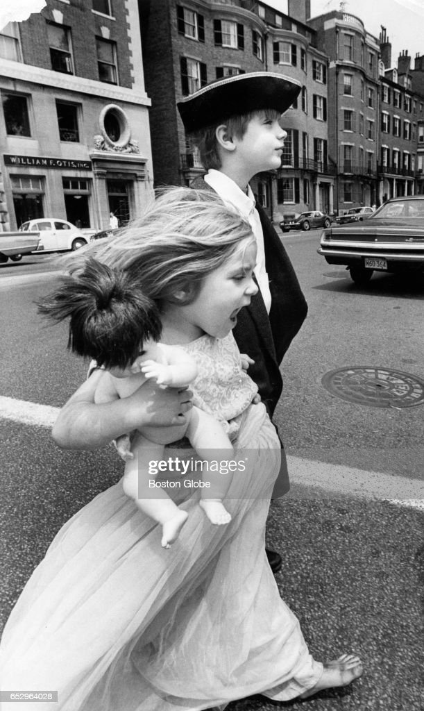 Rebecca Scovel, 4, and her brother Christopher, 8, cross Beacon Street on their way to a Summerthing dress-up parade on the Boston Common in Boston on Jul. 15, 1970.