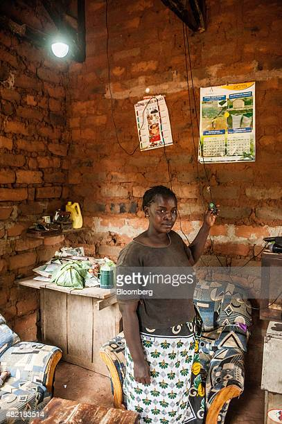 Rebecca Wambua a village resident demonstrates an electric LED lightbulb powered by an MKopa Solar payasyougo solar power system at her home in the...
