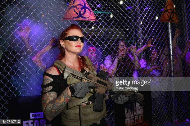 Rebekah Hall dressed as the character Agent Scarlet with other actors dressed as zombies perform during the Fear the Walking Dead Survival attraction...