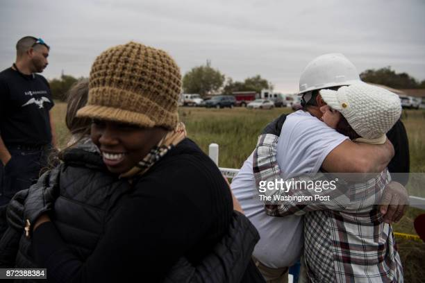 Rebekah Weigner and Sharaell Treloar left hug while Amy Parks and Greg Zanis hug after Rev Van Jordan of Port Arthur Texas led a group prayer while...