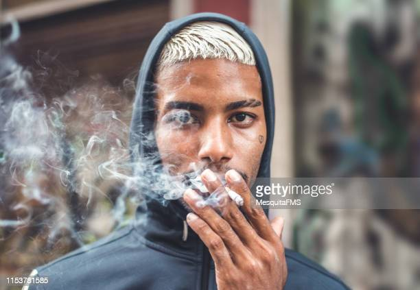 rebel boy smoking on the street - smoking stock pictures, royalty-free photos & images