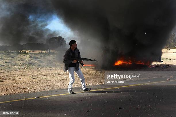 A rebel fighter advances on the front line against Libyan government forces on March 2 2011 in alBrega Libya The rebels drove out troops loyal to...