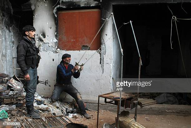A rebel fighter aims a makeshift slingshot at proregime fighters during clashes in the eastern Syrian town of Deir Ezzor on March 13 2014 Syria's...