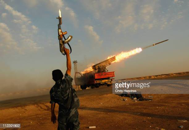 A rebel fighter celebrates as his comrades fire a rocket barrage toward the positions of troops loyal to Libyan ruler Muammar Gaddafi April 14 2011...