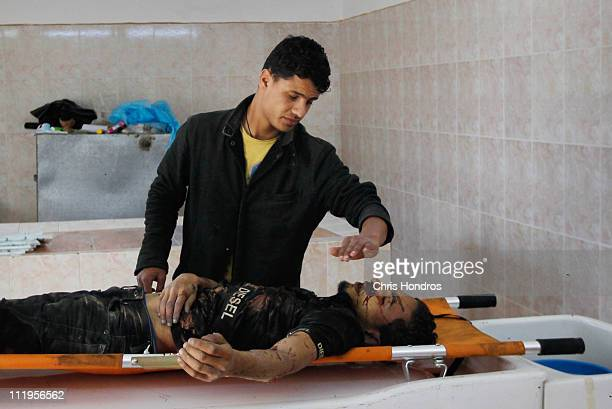 A rebel fighter closes the eyes of a comrade in the Ajdabiyah morgue after he was killed during clashes with government troops April 10 2011 in...