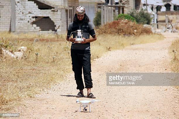 A rebel fighter controls a drone on July 13 2016 in the central Syrian rebelheld town of Talbiseh during the rebel fighter's operations to target the...