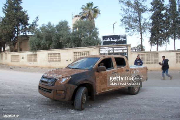 A rebel fighter drives past the local council building in the village of Rahbet Khattab in the Hama province on March 23 2017 Jihadists and allied...