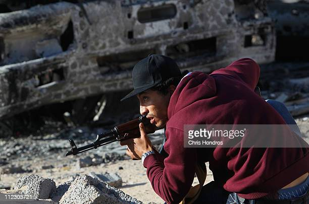 A rebel fighter ducks from incoming fire at the front lines on Tripoli Street in downtown Misrata April 18 2011 in Misrata Libya Tripoli Street once...