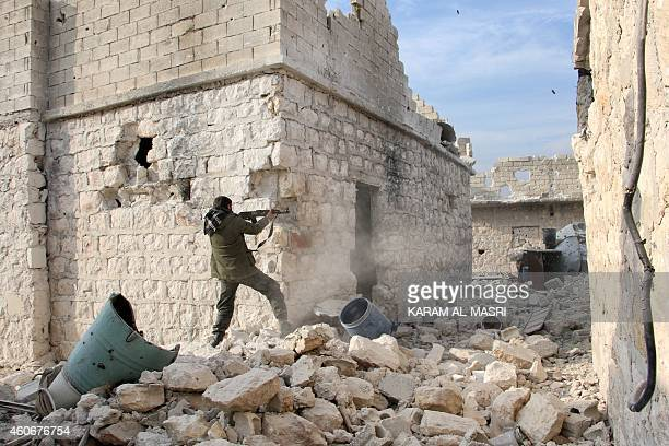 A rebel fighter fires his weapon on the frontline during the battle against progovernment forces for control of the Handarat region located just...