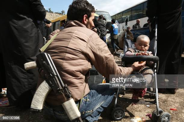 A rebel fighter from Eastern Ghouta carrying a weapon plays with an infant after arriving in Qalaat alMadiq some 45 kilometres northwest of the...