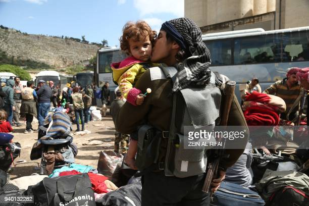 TOPSHOT A rebel fighter from Eastern Ghouta holds his weapon as he kisses a child after arriving in Qalaat alMadiq some 45 kilometres northwest of...