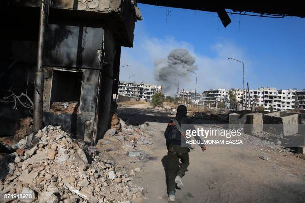 TOPSHOT A rebel fighter from the Ahrar alSham brigade runs as smoke billows in the background in the rebelheld besieged town of Harasta in the...