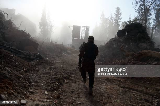 A rebel fighter from the Ahrar alSham brigade walks past the debris of damaged buildings in the rebelheld besieged town of Harasta in the Eastern...