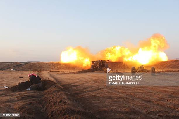 TOPSHOT A rebel fighter from the Jaish alFatah brigades fires artillery during clashes with Syrian progovernment forces near the village of Om...