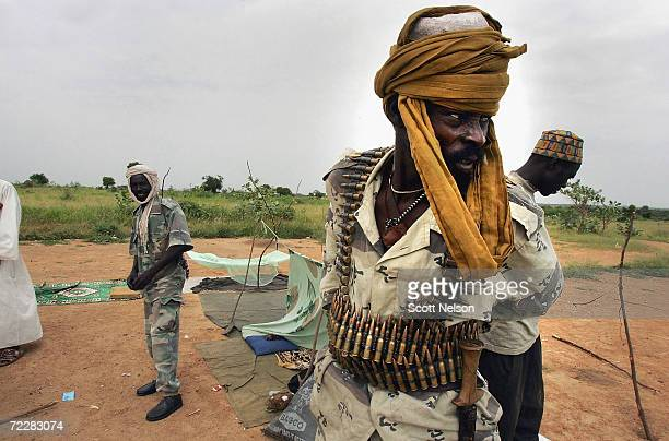 A rebel fighter from the Sudanese Justice and Equality Movement starts his morning by draping himself in ammo at their base in the Darfur region of...