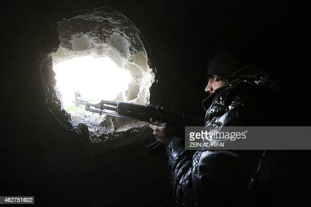 A rebel fighter holds a position in alMayasat a rebelcontrolled area near the industrial zone of the northern Syrian city of Aleppo on February 4...